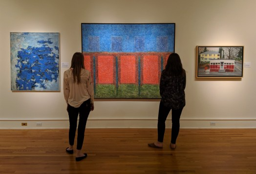 Two museum goers look at Ernst's painting. An abstract canvas, the blue sky gives way to four red rectangles that look like doors or panels to a fence. Beneath them is layered greens, suggesting grass.