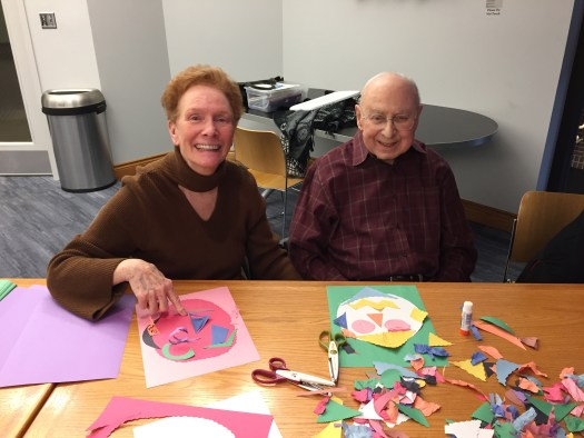 Judy and Dick Gillman sit at a table and work on their self-portraits made of cut paper.