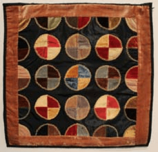 This quilt has five circles in five rows, with the first and second row only half circles as they are cut off by the border of the quilt. The circles are patchworks of fabric, various colors. Cut into quarters, each quarter is a different color.