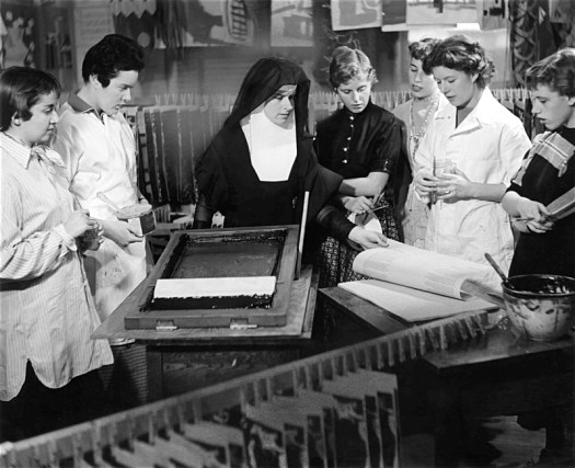 Cortia Kent, dressed in her habit, teaches students silkscreening techniques.