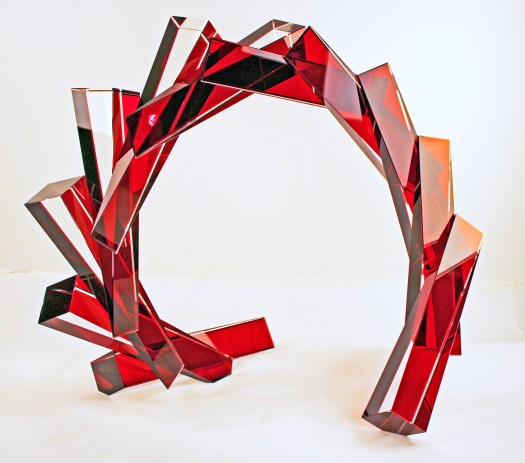 An abstract, red glass sculpture that uses long, rectangular strips to create a fragmented half circle.
