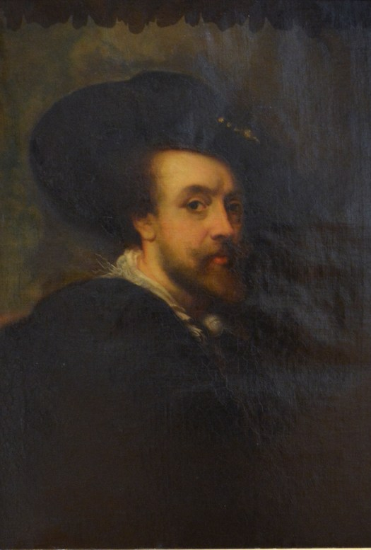 A self-portrait of painter Peter Paul Rubens. Against a dark, muddy background, Rubens wears a black cloak and large black hat. At three-quarters view, his eye looks out at the viewers.