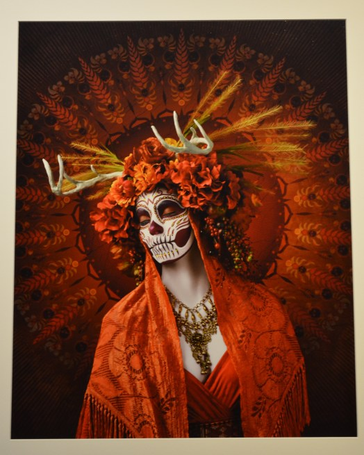 This photo shows a woman in orange dress and orange shawl draped over her shoulders. Her face is painted white to look like a skeleton and her hair, which is also covered by the shawl, is covered too by a floral headband. The floral headband includes antlers from a deer.