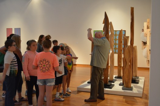 Students from J.E. Ober Elementary enjoyed a fee-free docent-guided tour through the museum, and they stand in front of a wood sculpture by Barbara Stanczak.