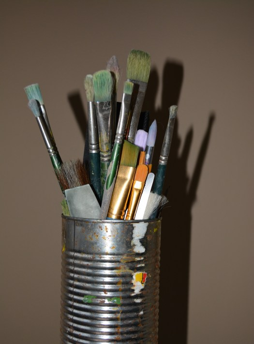 A can holding paintbrushes in all shapes and sizes.