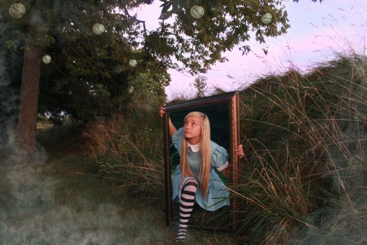 A photograph of a girl with long, blonde hair in a field. Dressed in a blue dress and white and black striped socks, she emerges from a frame.