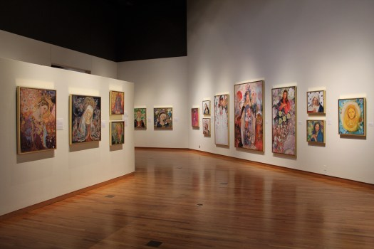 Mary Tullis' paintings, which are interpretations of the Virgin Mary, hang in a brightly lit gallery. Each painting receives its own overhead light, like an angelic halo, because paintings are not susceptible to damage from lights.