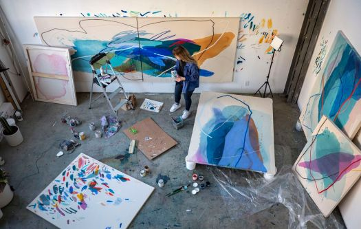 Artist Heather Day is shot from above in her studio, providing a birds-eye view of her work. Paints and canvases litter the floor, as she works on multiple paintings at once.