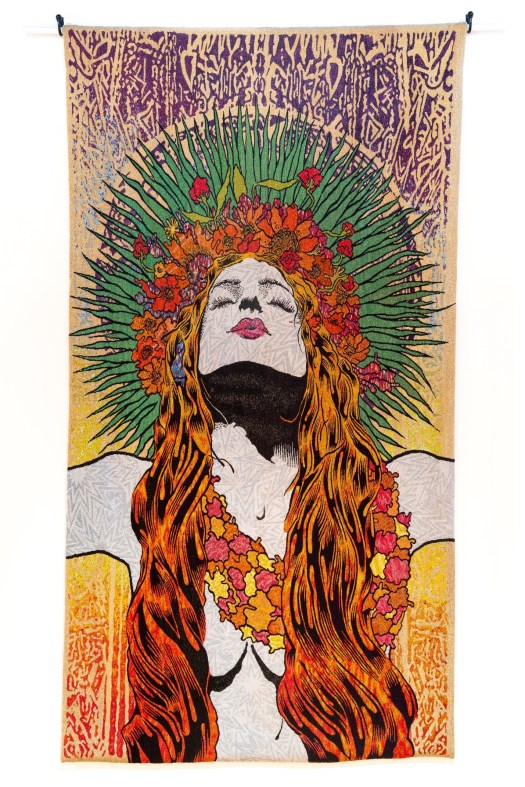 A woman with long, red hair that partly covers her breasts raises her arms and looks skyward. She wears a lei of flowers, and more flowers make up her headband. She has a green arc of leaves around her head.