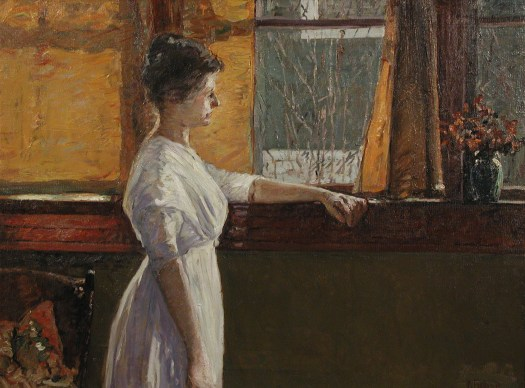 A young woman in a white dress stares out the window of her home to a gray day.