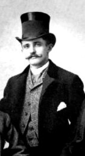 A black and white photograph of Theodore Thieme. He wears a suit and top hat. His large overcoat is black, and he sports a moustache.