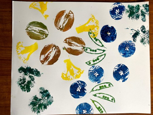 The completed work includes the green peapods, blue apples, yellow broccoli, and green radish leaf.