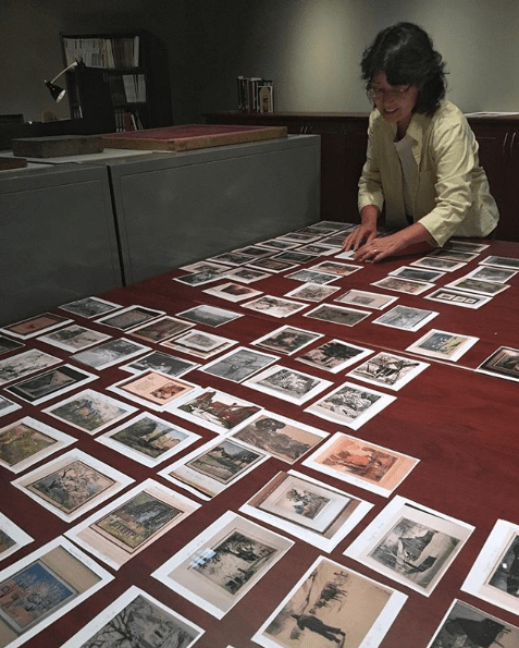 Curator Sachi Yanari-Rizzo stands at the head of a large oak table. In front of her are pictures of over 40 prints by Brown County, Indiana artists. She is using her oak tables to sort the photos, or curate them into groups, before hanging the actual works in the exhibition.