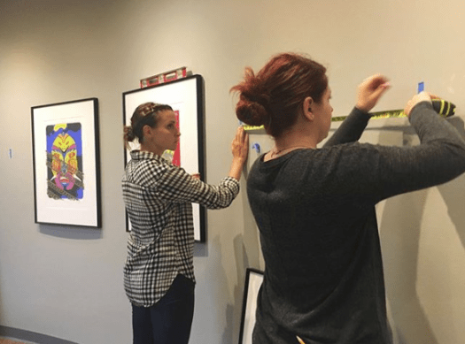 Elizabeth Kilmer and Lauren Wolfer hold a measuring tape against the wall as they work to hang artworks for a curated exhibition at Indiana Tech.