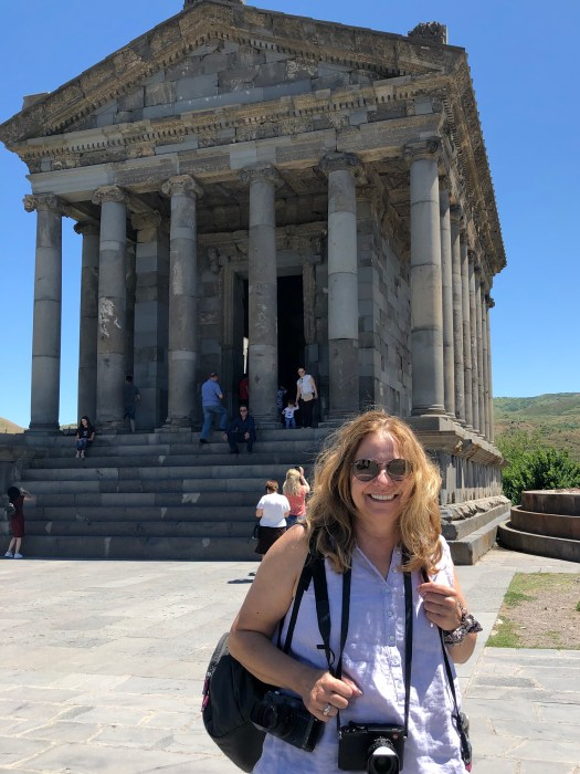 The artist stands, cameras around her neck, in front of the Temple of Garni in Armenia.