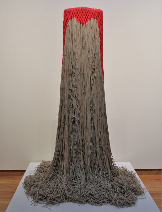A tall cascading network of knotted, natural hemp fibers. The many, long fibers are suspended from an metal armature and fall into mounding heaps on the floor.  At the very top is a short cap of red wool fibers. The sculpture stands in the center of a pedestal with no support.