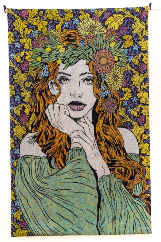 A portrait of Demeter, she stands with her head resting in her hand, a garland of flowers on top of her head of long, flowy red hair. She wears a shoulder-less green dress. The background is a mix of green, blues, and purple flowers and leaves. Her bright green eyes are open and stare out at the viewer.