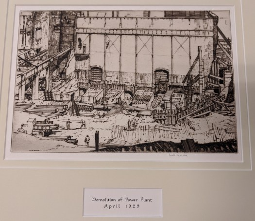 This etching shows the demolition of a power plant. Works stand in the foreground moving planks and loading them onto a truck. The majority of the composition shows the foundation of where the building once stood, with only it's back wall still intact.