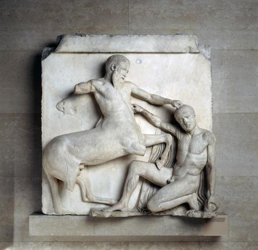 A centaur rests his fist atop a kneeling man, as the kneeling man's fist makes contact with the centaurs muscled stomach. Due to time, the centaurs stone arms and legs, which would have come off the background, have fallen off.
