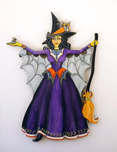 A single witch stands with her arms outstretched, in one is a mouse and in the other is a broom. She wears a purple dress and a spiderweb cloak. Her green skin stands out against the black hat adorning her curling, black hair, that is topped by an owl.