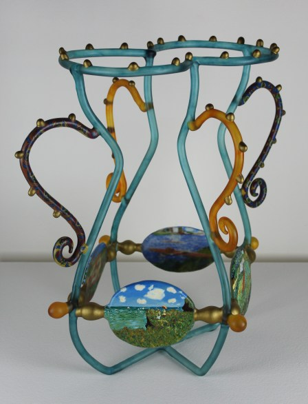 A glass sculpture of an urn, along the bottom are glass ovoid's affixed to the open sides, painted with Impressionist scenes: landscapes and everyday figures.