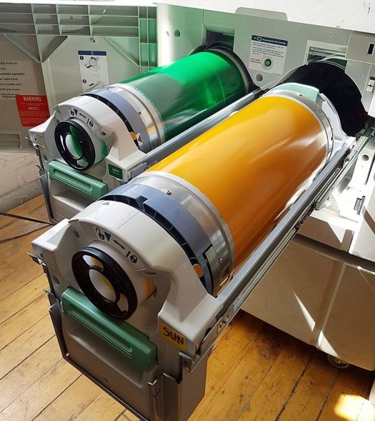 A photo of ink tubes, colored green and orange, being inserted into the Risograph.