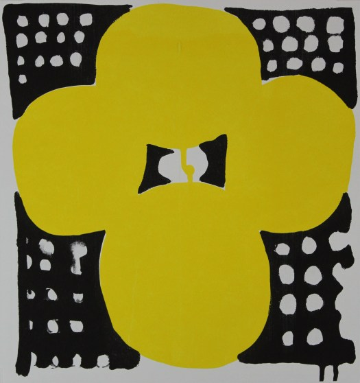 A print of a large, yellow flower. In each of the four corners are white polka-dots.