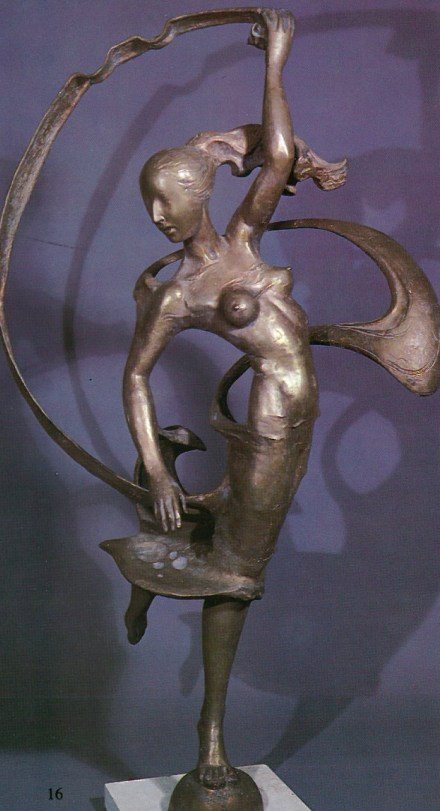 A bronze sculpture of a dancer, twirling on one foot. Her right arm is raised in the air and holds the end of a fabric that is unfurling from her skirt. Naked from the waist up, her left arm forms a diagonal line. Her face is turned away from the viewer, and her hair, pulled up, is blown in the wind that also twirls the fabric.