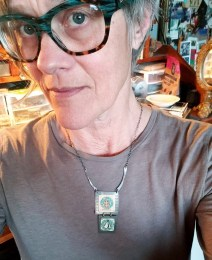 Portrait of the artist, Lisa Vetter, in glasses and wearing a necklace she made.