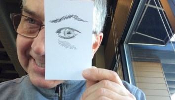 A photograph of the artist. He wears glasses and smiles at the camera. In his right hand, a quick sketch of his eye covers his right eye.