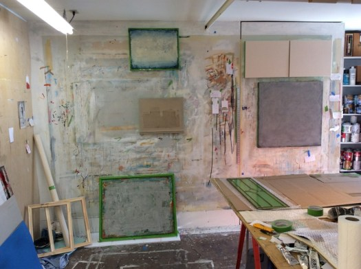 Another photograph of the studio, with works hanging on the wall in different stages of completion.