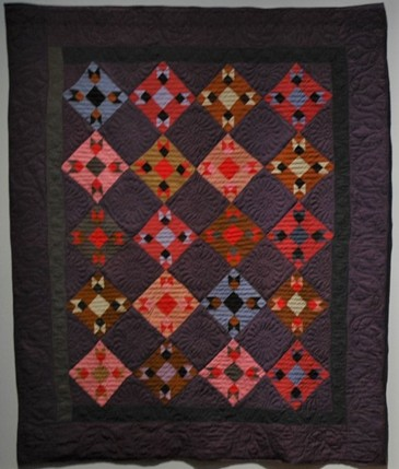 "The ""Wandering Foot"" pattern is a set of diamonds with a diamond center. The background is a deep purple with a black, inner border. The diamonds are multiple colors: pink, blue, red, and green which shows how leftover materials were repurposed for quilts."