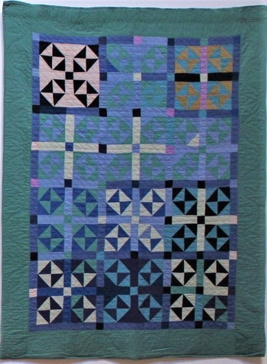 An aquamarine quilt, the blues and purples and greens match well. Square windows create a snowflake-like pattern.