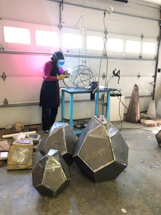 The artist in her studio welding a steel armature to support her resin sculptures.