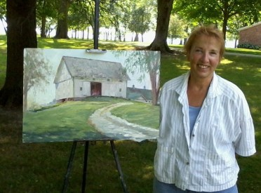 The artist pictured outside with one of her paintings.