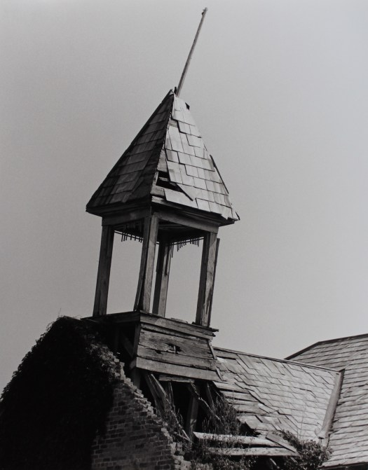 A close-up black-and-white photograph of a schoolhouse shows the bell tower, tilting forward. The roof beneath is either crumbling or already gone, and the bricks on the side are falling as well.