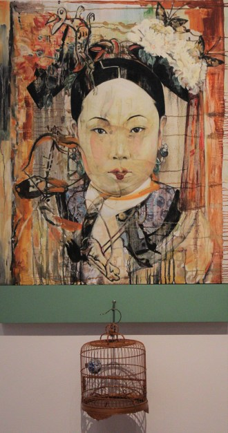 A painting shows the head and shoulders of a concubine from the Qing Dynasty. She makes direct eye contact with the viewer, wearing makeup and an elaborate headdress. Beneath the work hangs a bamboo, ornamental bird cage.