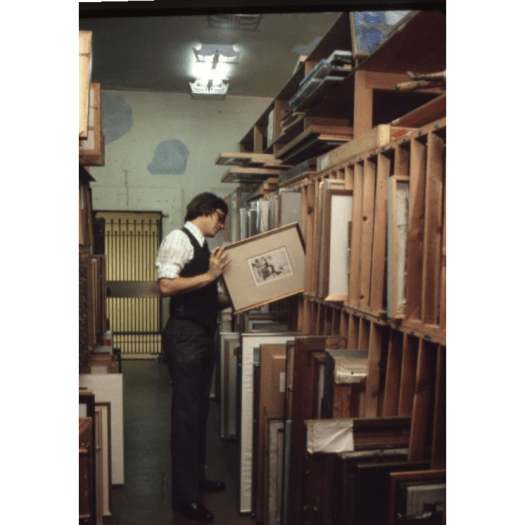 A photograph from 1980 show a FWMoA Curator looking at paintings in storage.