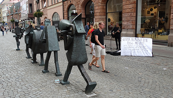 """Peter Ahlborg speler på Södergatan i Malmö, vid det berömda konstverket """"Optimistorkestern"""" skapad av Yngve Lundell. Foto: Privat"""