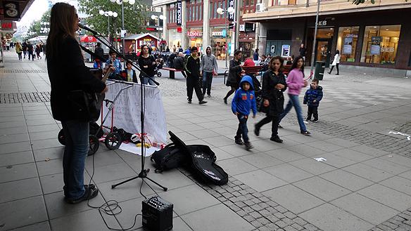 Peter spelar på Södergatan i Södertälje. Lägg märke till   den unga killen mitt i bilden som fascinerat följer Peter. Och som   inte ville följa med sin mamma när hon skulle gå. Foto: Carina Ekman