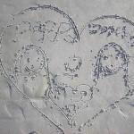 Min dotter ritar ett jättefint hjärta av oss på sand stranden i Askim