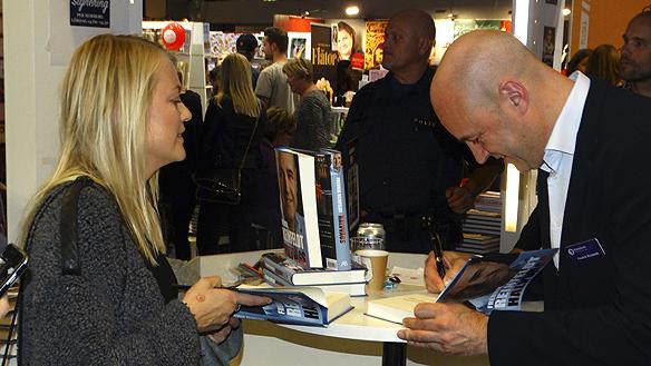 Ett litet smile visar sig under Bokmässan 2015 när Fredrik Reinfeldt skriver autografer för brinnande livet. Foto: Peter Ahlborg
