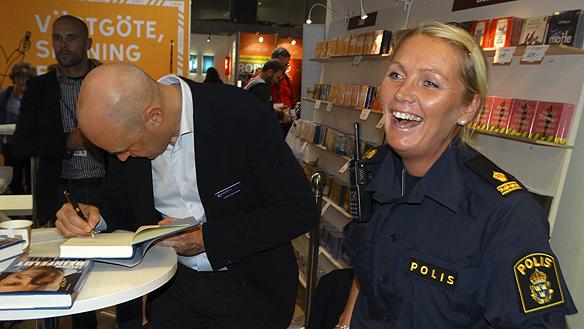 En glad polis är en bra polis. Denna kvinnliga polis var mycket glad att hon fick chansen att träffa Fredrik Reinfeldt och fick hans bok signerad under bokmässan 2015. Foto: Peter Ahlborg