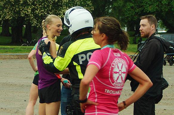 Motorcykelpolisen som har eskorterat Sara Christiansson under tävlingen i Vårruset i Vänersborg 2018 går fram här och ger vinnaren Sara en klapp på axeln. Foto: Peter Ahlborg.