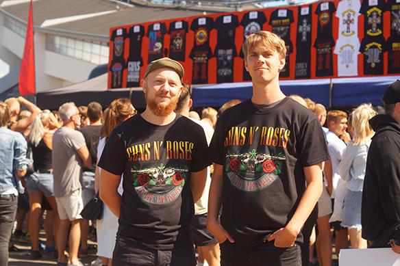 Två glada fans vid 15-tiden idag utanför Ullevi. De haregna biljetter med sitt namn på. Men det finns en del människor som harköpt andrahandsbiljetter och inte har sittnamn på biljetterna. Då kan det bli problem att komma in i och med de nya reglerna,förklarar Peter Ahlborg här för dessa två Guns N' Roses-fans. Foto: Peter Ahlborg