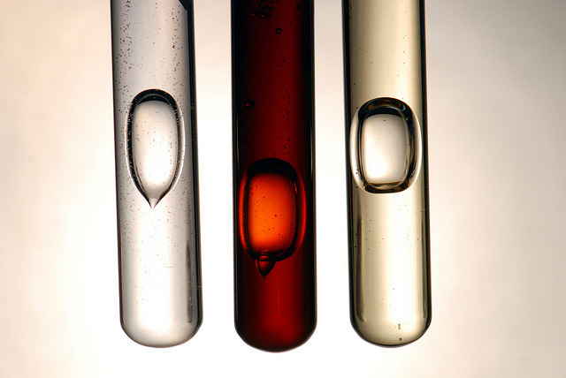 Three test tubes containing bubbles, the middle of which is red