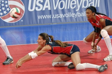 A volleyball player dives to bump the ball while her teammate calls