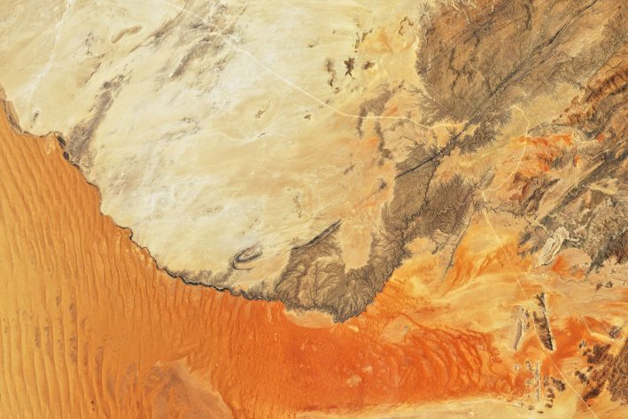 Satellite image showing the northern extent of the Namib Sand Sea in orange red and the solid, rocky land that forms its border.