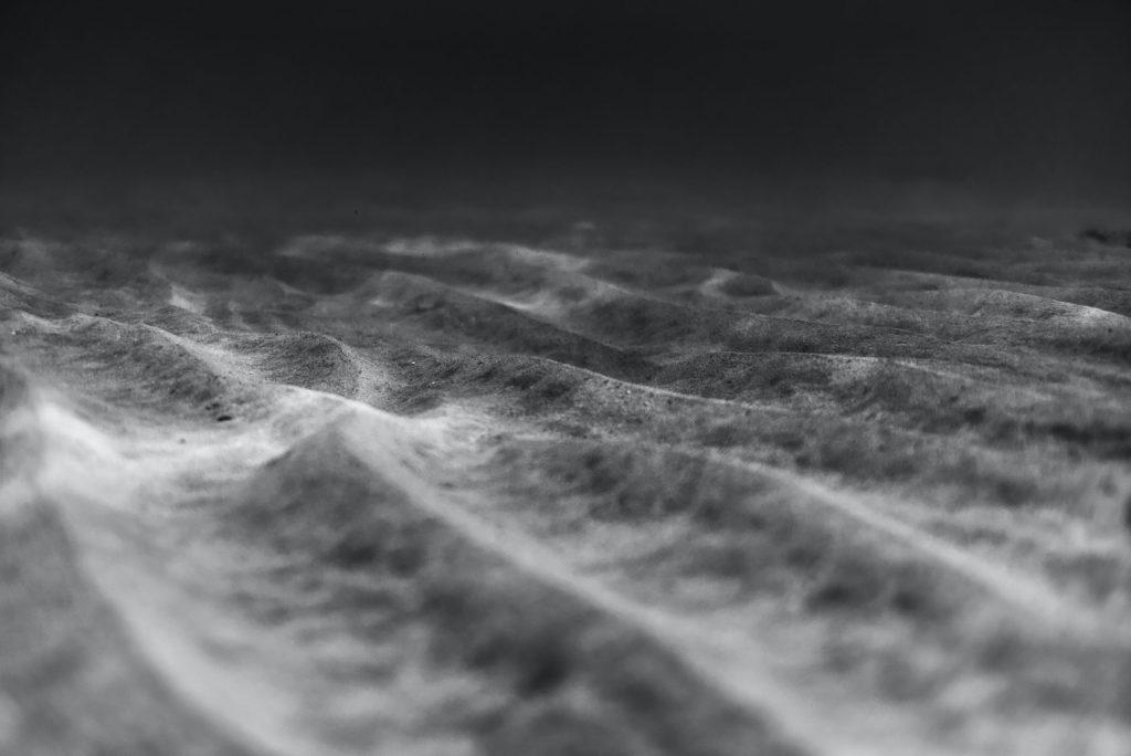 Sand ripples underwater.