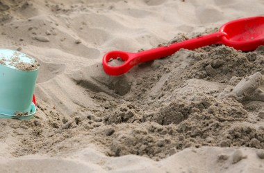 A child's bucket and shovel in the sand.